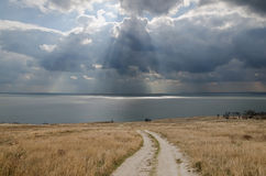 Dirt road leading to the sea and the dramatic clouds over the se Royalty Free Stock Photos