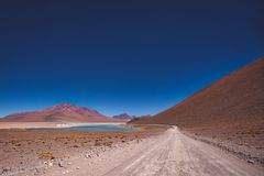 Dirt road leading to the Siloli salt flats. Through arid desert scenery and mountains, Bolivia, South America stock images