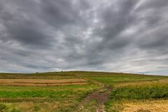 Free Dirt Road Leading To The Top Of A Green Hill At Summertime, Gathering Storm Clouds Stock Photos - 193594683