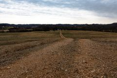 Dirt road in rural Appalachia. Dirt road leading through a winter pasture to a farm in rural Appalachia stock image