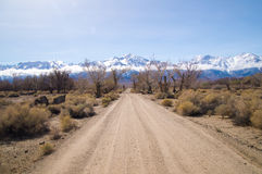 Dirt road leads to snow covered Sierra Nevada mountains in Sprin Royalty Free Stock Photos