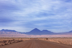 A dirt road leads to the Volcano Licancabur in San Stock Photos