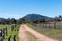 Dirt Road Lined with Wooden Fence Leading to Mount Woodson stock images