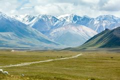 Dirt road in majestic Tien Shan mountains Stock Photos