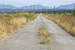 Dirt Road and Major City Stock Photography