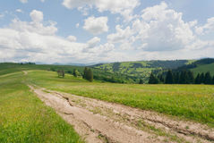 Dirt road on mountains under blue sky. Rural landscape with clouds Stock Photos