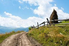 Dirt road near the wooden fence in the Ukrainian Carpathians Royalty Free Stock Photos