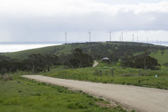 Dirt Road, Ocean and Wind Turbines, Fleurieu Peninsula, South Au. South Australian bush dirt road with wind turbines busily generating electricity on the hills Royalty Free Stock Photos