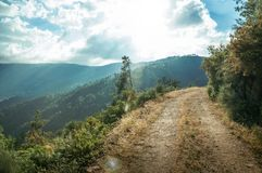Dirt Road On Hilly Terrain In Sundown Royalty Free Stock Images