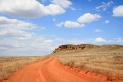 Dirt road orange prairie, going to the blue sky Stock Images