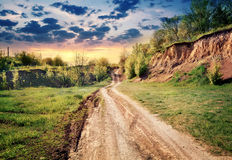 Dirt road passing by earthen cliff to the sun Stock Photography