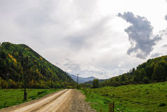 Dirt road passing among the forested hills Stock Image