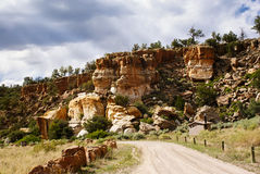 Dirt Road Past Rocky Desert Cliffs Royalty Free Stock Images