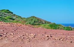 Dirt road in Porticciolo. Red dirt road in Porticciolo, Alghero Stock Photos