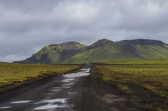 Dirt road after rain and moss-covered volcanic mountains. Landma. Nnalaugar. Iceland Royalty Free Stock Photography