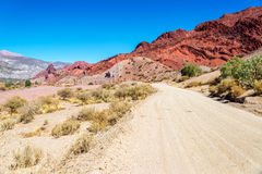 Dirt Road and Red Desert Hills in Bolivia Royalty Free Stock Images