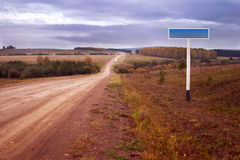 Dirt road and road sign. Autumn landscape: cart-dirt road and an empty road sign Royalty Free Stock Image