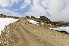 Rocky road to the top of a rocky mountain covered with snowdrift royalty free stock images