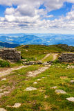 Dirt road and ruin of stone wall on the top of Pip Ivan mountain in Carpathians, nature landscape, Ukraine. Royalty Free Stock Photos