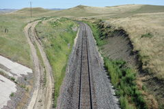 A dirt road running beside train tracks in wyoming. A picture taken from a bridge showing a road and train tracks snaking through the prairies Royalty Free Stock Photography