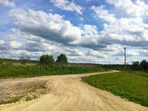 Nature. Cumulus clouds. Meadow. Dirt road Stock Photo