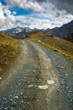 Dirt road in scenic alpine landscape and dramatic sky Stock Photography