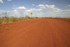 Dirt road sign. Red Australian rural road with a road sign for dangerous turn. Tanami road, Northern Territory.  Australia Stock Photo