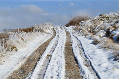 Dirt Road in a Snowy High Mountain Plateau Stock Photo