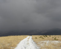 Dirt Road in a Snowy  Mountain Plateau. Brightly lit snowy country road leading to dark stormy sky Royalty Free Stock Images