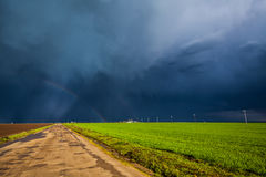 Dirt road and storm sky. Dirt road and dark storm sky, rainbow visible in distrance Royalty Free Stock Photography