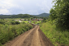 Dirt road to new village in Altai. Royalty Free Stock Photo