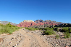 Dirt road to red mountain Stock Photography