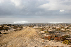Dirt road to the sea. West coast, Hondeklip Bay, cloudy,misty morning Stock Images