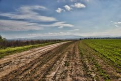 Dirt road to the village. Cloudy sky, Slovakia Royalty Free Stock Photo