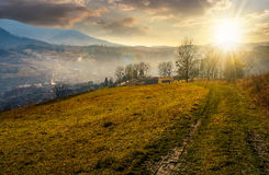 Dirt road to village down the hill at sunset. Dirt road to village down the hill. trees on hillside and village in valley in autumnal countryside landscape in Stock Image