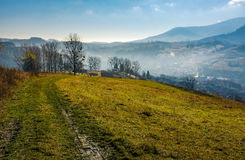 Dirt road to village down the hill. Trees on hillside and village in valley in autumnal countryside landscape Stock Photos