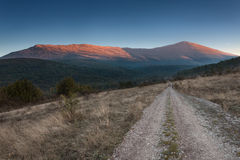 Dirt road towards the mountain at dawn Stock Images