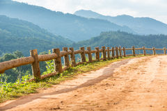 Dirt road track. On remote mountain with wooden barrier and cascade of green mountains in the background stock images
