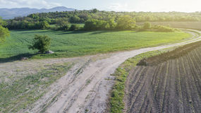 Dirt Road Between Two Farming Fields. Old Dirt Road Between Two Farming Fields In Sunny Day Royalty Free Stock Images
