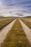 Dirt road under a cloudy sky Stock Photos