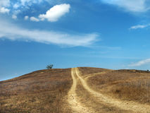 Dirt road up the hill Royalty Free Stock Image
