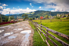 Dirt road through the village to the mountains Stock Photography