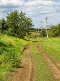 Dirt road in the village, spring day and green grass around. Royalty Free Stock Photo