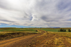 Dirt road and white clouds Royalty Free Stock Photos