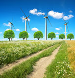 Dirt road with wind turbines. Stock Images