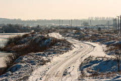 Dirt road in winter time, along the river Olt. A lonely dirt road along the river Olt. Mainly used by large trucks carrying sand and stone, this is an important Royalty Free Stock Photo