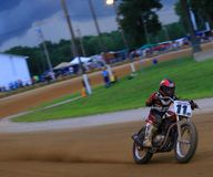 Dirt track bike racing event. Dirt is kicked up in the air as the racing bike finishes the turn Stock Photos
