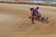 Dirt track bike racing event. Dirt is kicked up in the air as the racing bike makes the oval turn Royalty Free Stock Image