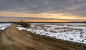 Dirt track through a field of snow going into the distance stock image