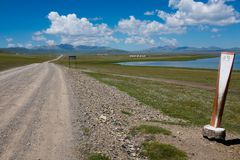 A Dirt Track by Song Kul Lake, Kyrgyzstan. A dirt track with a distance marker next to Song Kul lake in Kyrgyzstan with a blue cloudy sky Stock Images